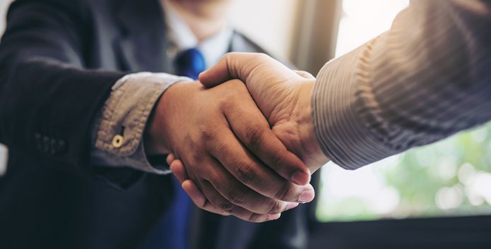 Two professionals closing a deal by shaking hands