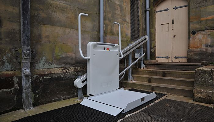 An inclined platform lift at the base of a small set of stairs outside Scotney Castle