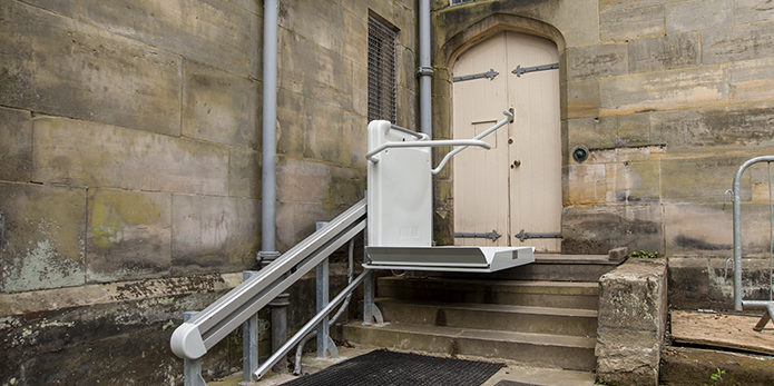An inclined platform lift assiting mobility down a few steps outside Scotney Castle