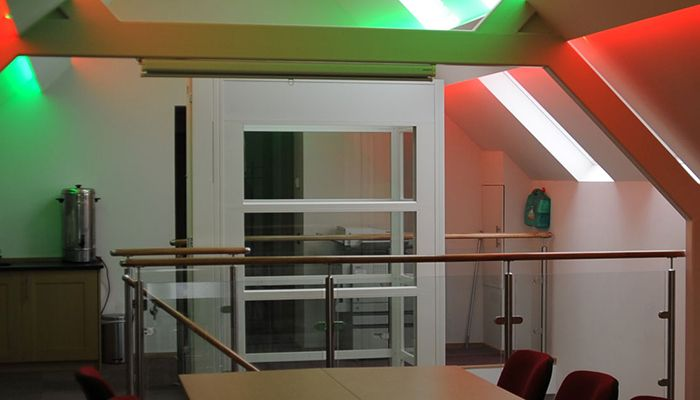 Kent Scouts meeting room with red and green lights showing the internal lift in the background