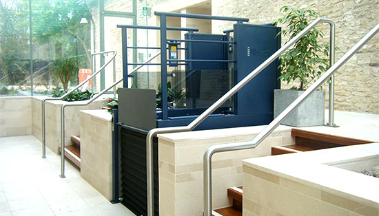 A low rise platform lift in use alongside an external staircase