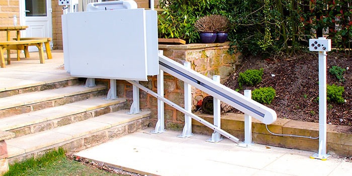 An inclined platform lift travelling down some garden steps