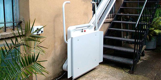 An inclined platform lift in a stationary folded position at the base of a staircase