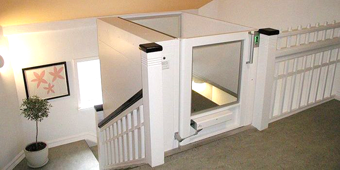 An enclosed platform lift located at the top of a staircase