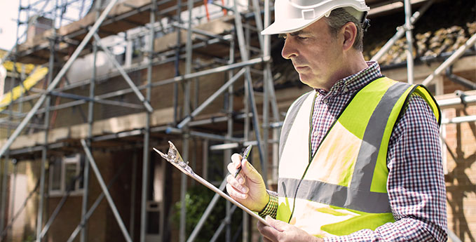 A construction worker examining a clipboard on a building site